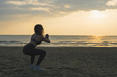 "Sporty athletic woman in sneakers and tracksuit squatting doing sit-ups on the beach on the sunrise background. Summer and freedom concept ""n"