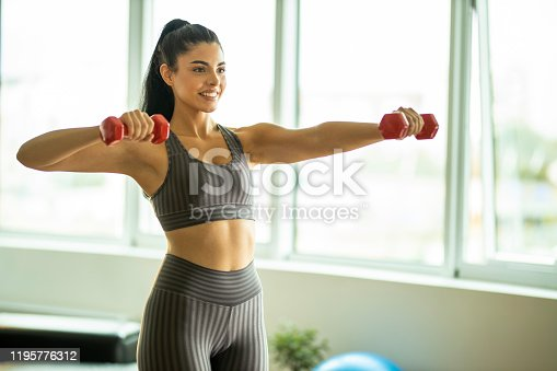 Sporty woman exercising with dumbbells at modern apartment to stay fit