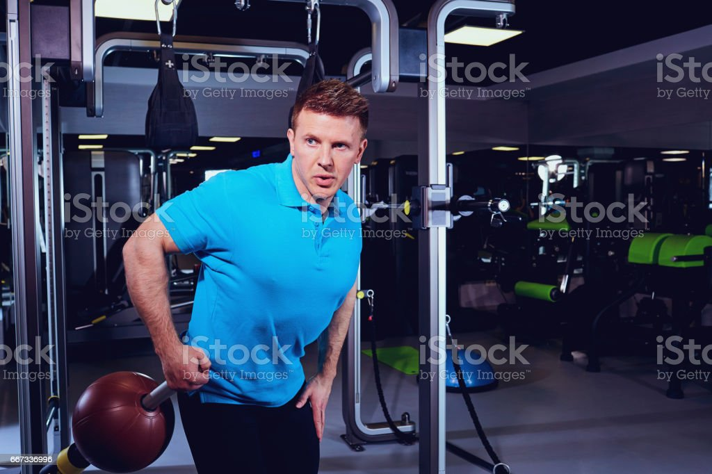 Ein sportlicher blonder Mann Übungen mit Ball in der Turnhalle – Foto