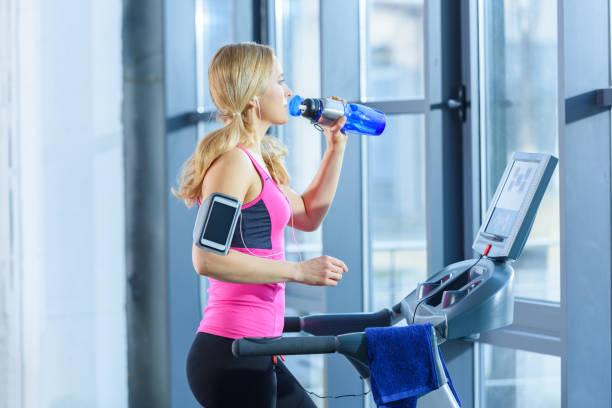 sportliche blonde frau training auf laufband und trinkwasser - armband water stock-fotos und bilder