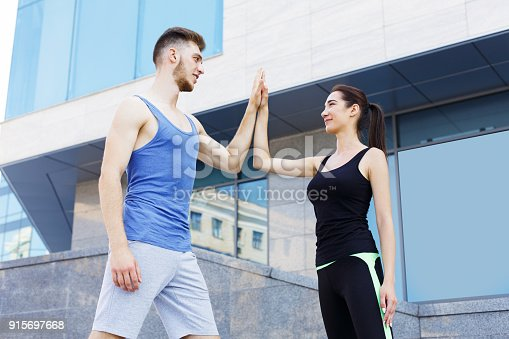 670054434istockphoto Sporty couple giving each other high five 915697668