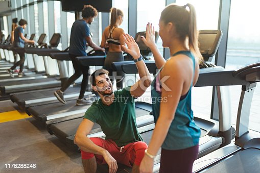 Sporty couple giving high five to each other at gym