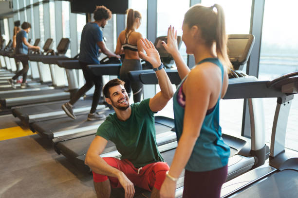 Sporty couple giving high five to each other at gym stock photo