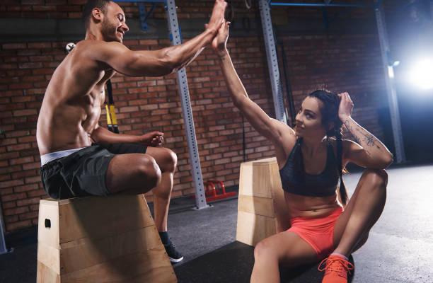 sporty couple high five at gym - ehepaar tattoos stock-fotos und bilder