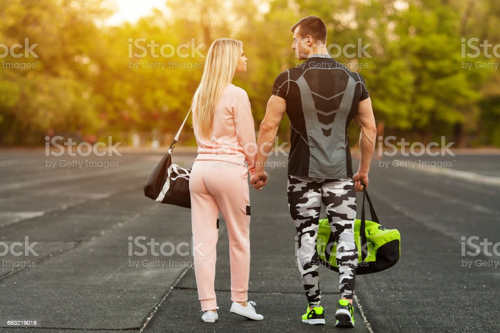 Sporty couple in sportswear together walking in the stadium. Athletic man and woman royalty-free 스톡 사진