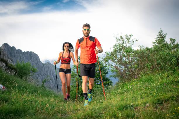 Sportliches Paar in den Bergen mit Nordic-Walking-Stöcken – Foto