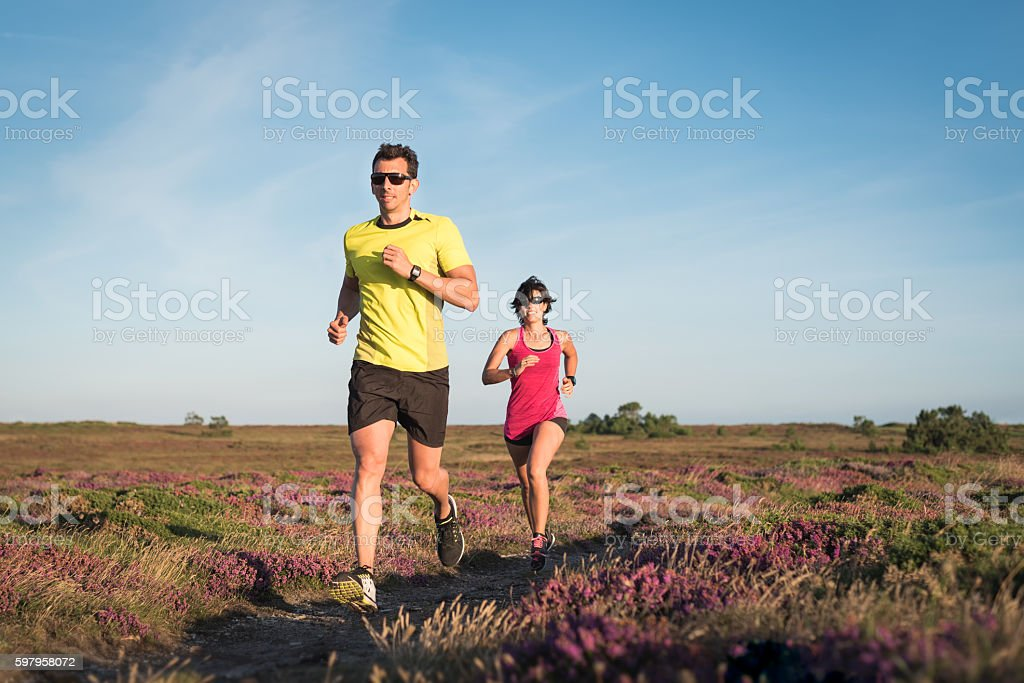 Sporty couple running outdoor cross country stock photo