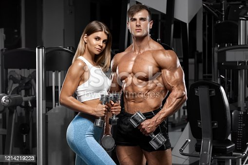 Sporty couple showing muscle and workout in gym. Muscular man and woman