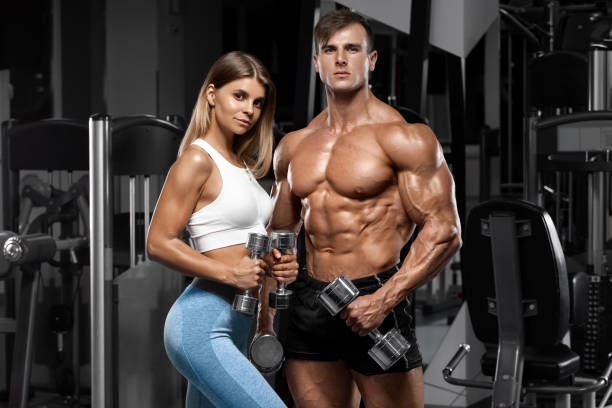 Sporty couple showing muscle and workout in gym. Muscular man and woman stock photo
