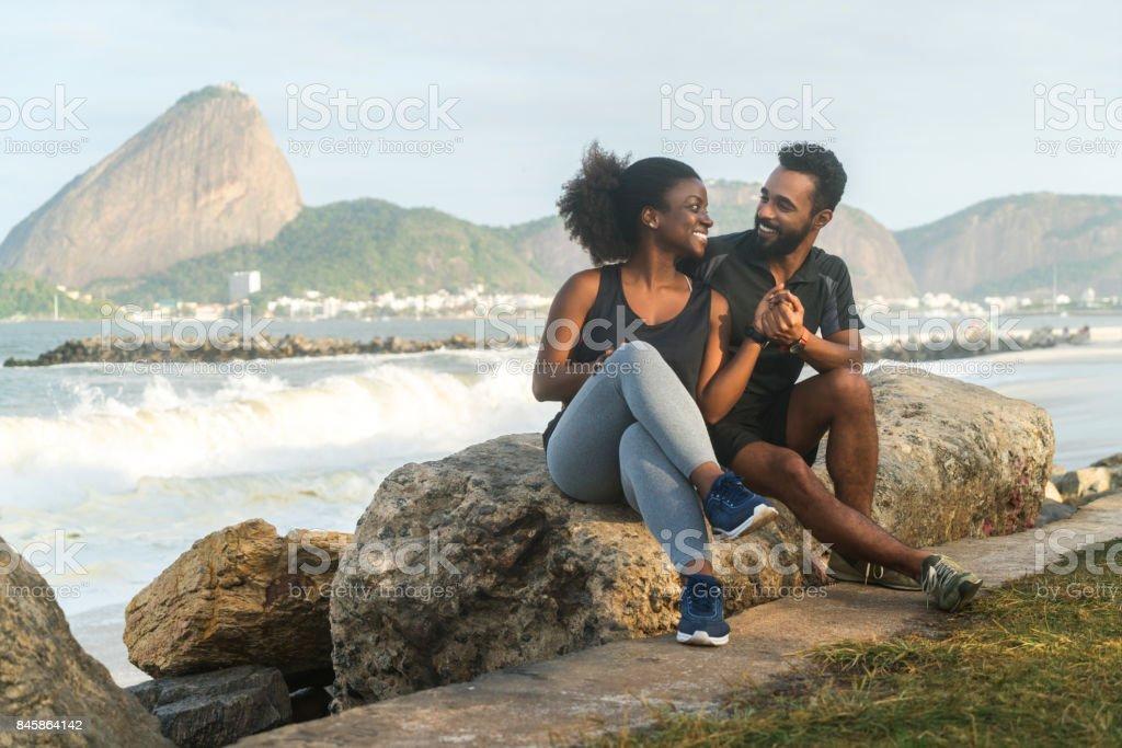 sportliches Paar sitzt auf Felsen am Strand – Foto