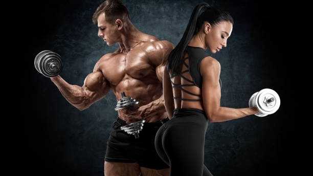 Sporty couple workout with dumbbells. Muscular man and woman showing muscles stock photo