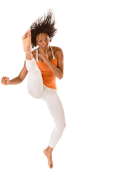 Sporty ethnic fitness woman jumping and kicking (motion blur) stock photo