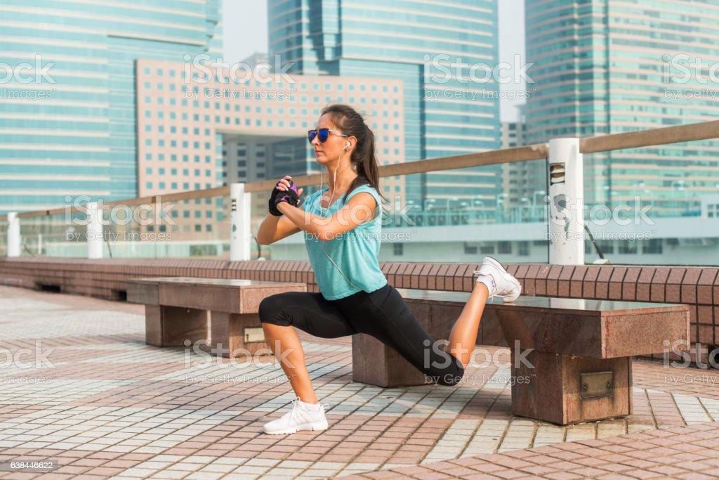Sporty female athlete doing single leg lunge exercise on bench stock photo