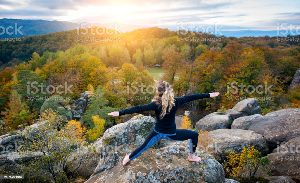 Sporty fit woman is practicing yoga on the top of the mountain stock photo