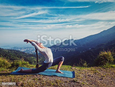 Vintage retro effect hipster style image of sporty fit woman practices yoga Anjaneyasana - low crescent lunge pose outdoors in mountains in morning