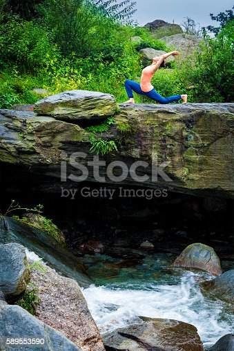Yoga outdoors - sporty fit woman practices yoga Anjaneyasana - low crescent lunge pose outdoors in mountains
