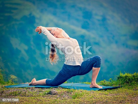 Yoga outdoors - sporty fit woman practices Hatha yoga asana Anjaneyasana - low crescent lunge pose posture outdoors in Himalayas mountains. Vintage retro effect filtered hipster style image.