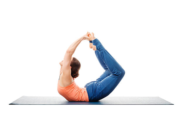 Sporty fit woman practices yoga asana Dhanurasana stock photo