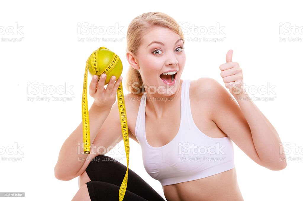 Sporty fit woman with measure tape fruit. Time for diet stock photo