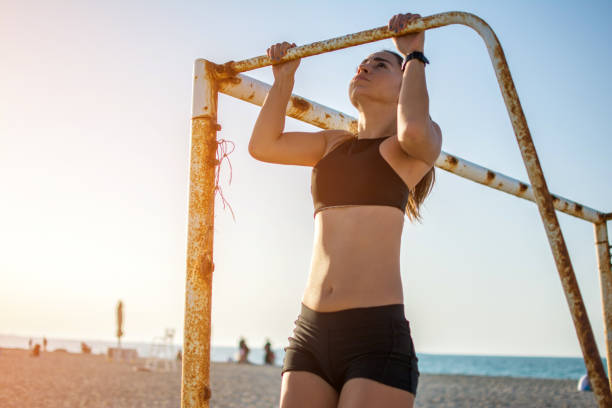 sporty fit young woman doing pull ups on metal goal frame on sandy beach during sunset. - horizontal bar stock photos and pictures