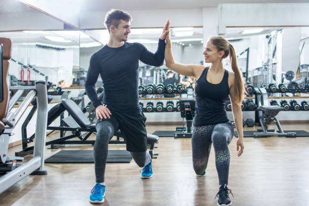 sporty fitness couple clapping hands together in the gym. - lunge stock photos and pictures