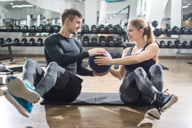 Sporty fitness couple doing abdominal exercises with medicine ball in the gym. stock photo