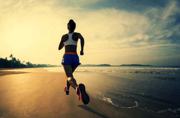 Sporty fitness woman runner running on sunrise beach stock photo