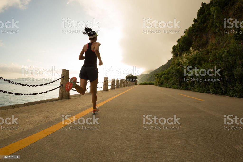 Sporty fitness woman running on sunrise seaside trail stock photo