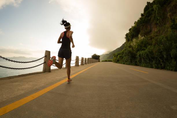 mujer de aptitud deportiva en camino de salida del sol junto al mar - maratón fotografías e imágenes de stock