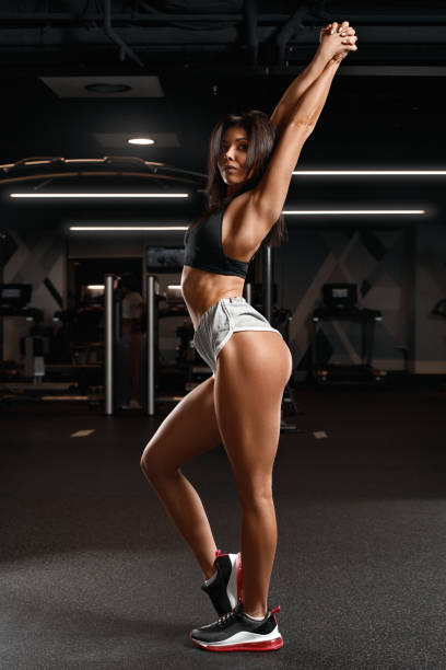 Sporty fitness woman with shaped glute in gym. Beautiful athletic girl stock photo