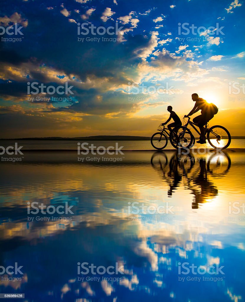Sporty friends.  bicycle on sunset. stock photo
