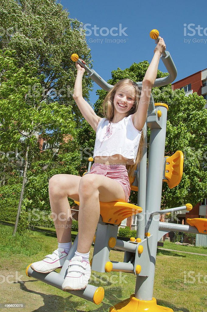 Sporty girl doing exercise outdoors stock photo
