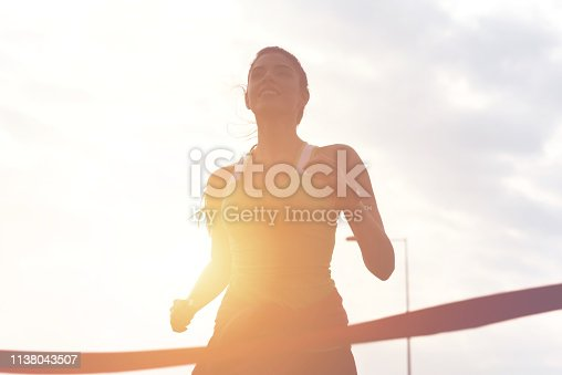 Portrait of attractive brunette with beautiful smile full of energy running to the finish line of race
