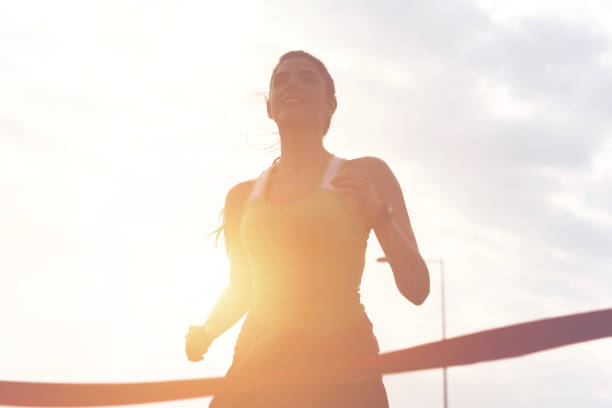 Sporty girl finishing the race Portrait of attractive brunette with beautiful smile full of energy running to the finish line of race women's track stock pictures, royalty-free photos & images