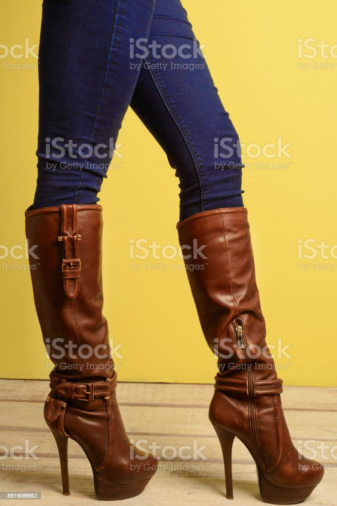 sporty girl in brown high-heeled boots and jeans stock photo