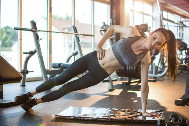 Sportliche Mädchen in Sportbekleidung tun Seite Planke Übungen auf Fitnessmatte im Fitness-Studio – Foto