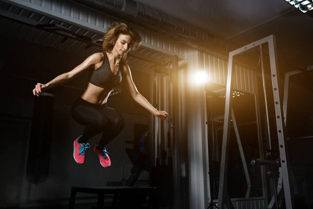 sporty girl jumping over some boxes in a cross-training gym stock photo