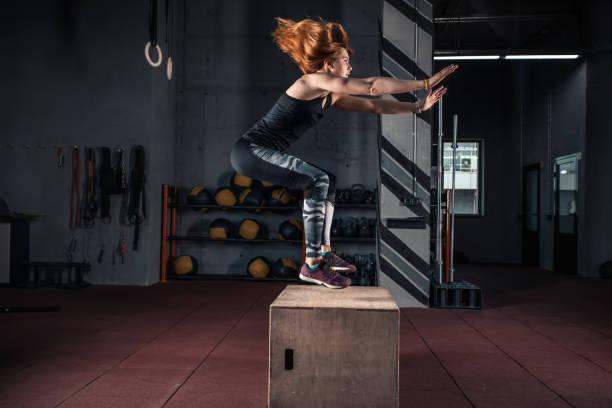 Sportliche Mädchen springen über einige Boxen in einem Cross-Trainings-Fitnessstudio – Foto