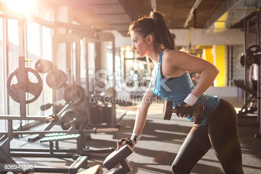 istock Sporty girl lifting weights in gym. 636947536