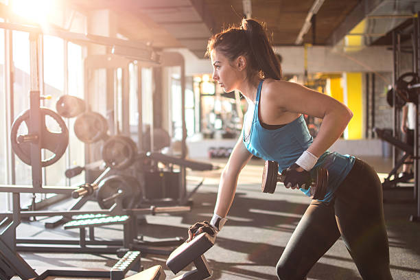 Sporty girl lifting weights in gym. stock photo