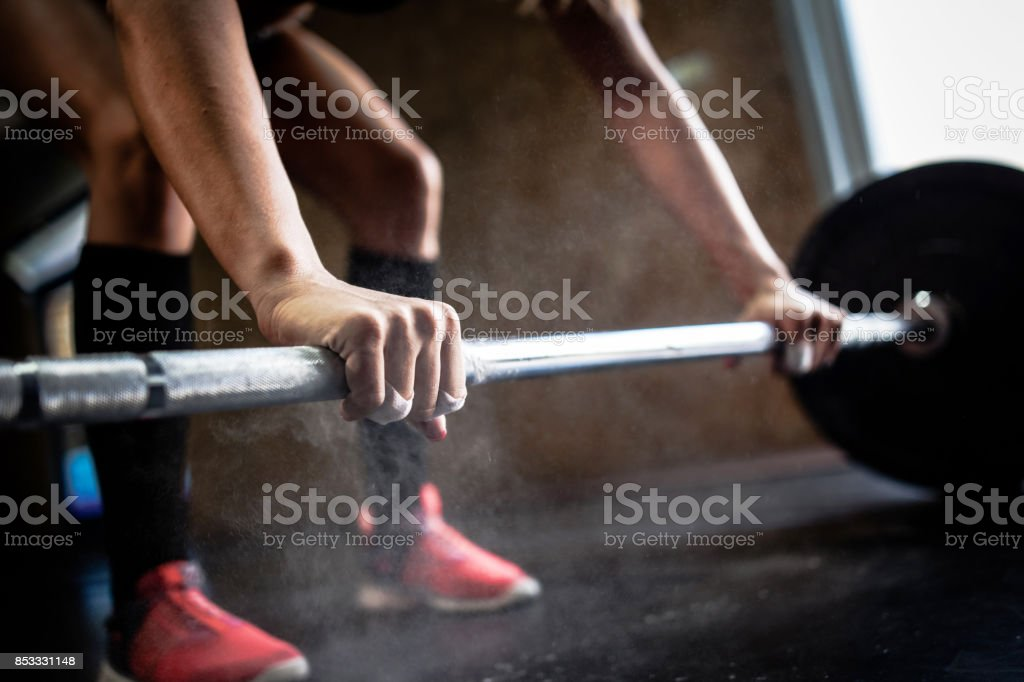 Sporty girl lifting weights in gym stock photo