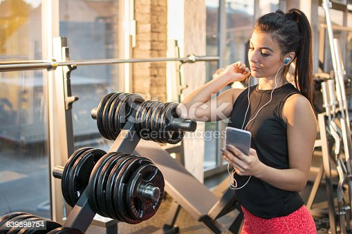 istock Sporty girl listening to music on smartphone at the gym. 639898754