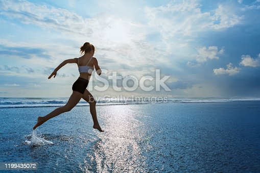 638628530 istock photo Sporty girl running by beach along sea surf 1199435072