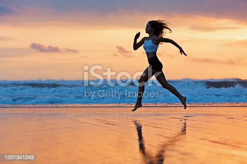 638628530 istock photo Sporty girl running by beach along sea surf 1201341043