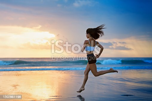 638628530 istock photo Sporty girl running by beach along sea surf 1202861198