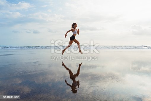 638628530 istock photo Sporty girl running by beach along sea surf 854594782