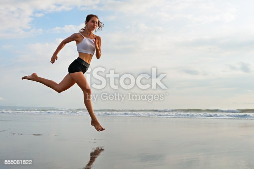 638628530 istock photo Sporty girl running by beach along sea surf 855061822