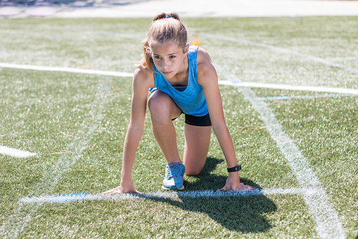 Sporty girl standing on her marks ready to run