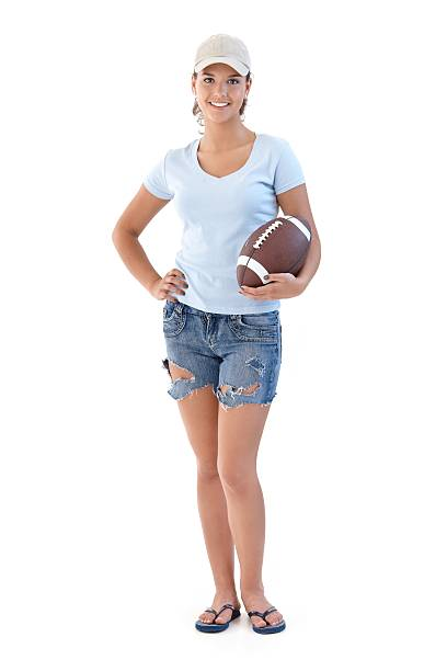 Sporty girl with American football smiling stock photo
