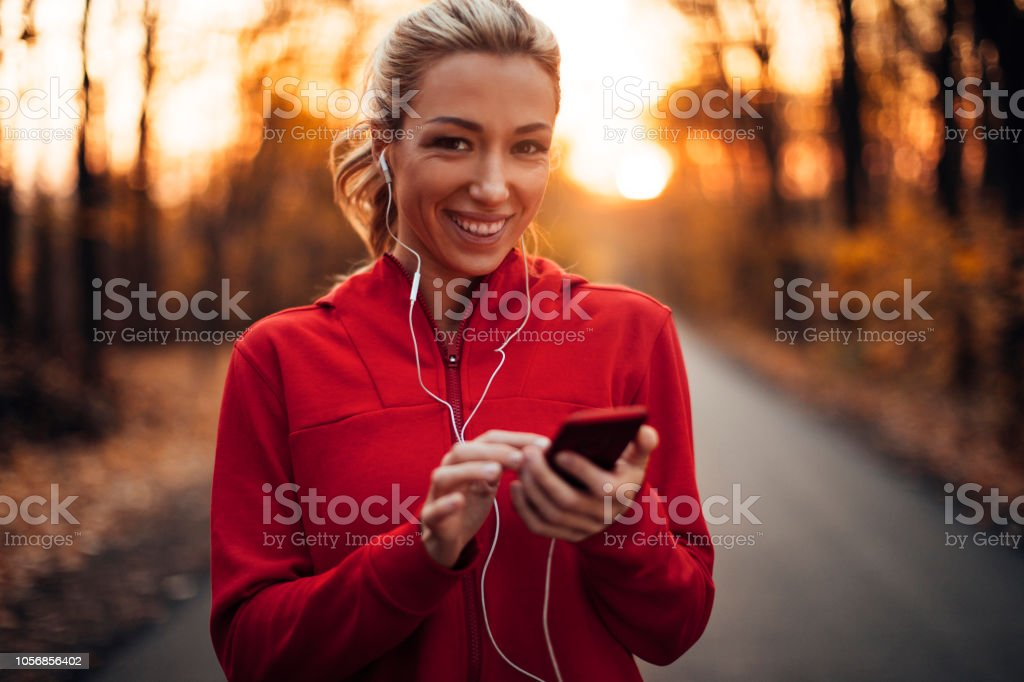 Sporty girl in the forest in Autumn using mobile phone and earphones
